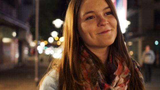 """Dieses Bild zeigt Hannah im Profil. Es ist ein Standbild aus dem Musikvideo für den Song """"Wenn Sie Lacht"""", wie sie lächelt und in der nächtlichen Stadt spazieren geht. Die Lichter leuchten unscharf im Hintergrund."""