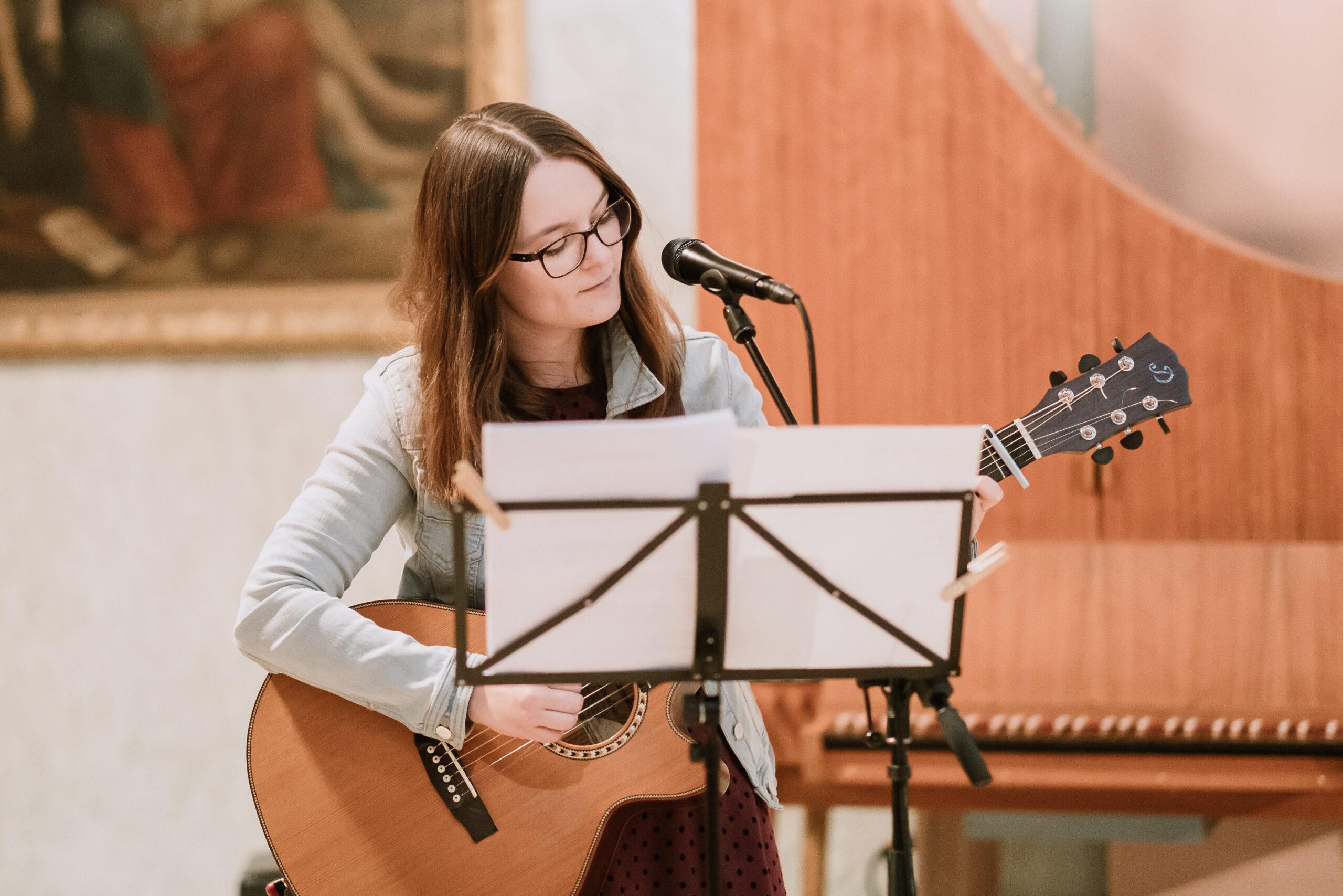 Bild von Hannah Stienen als Hochzeitssängerin in NRW, wie sie live in einer Kirche singt und sich auf der Gitarre begleitet.