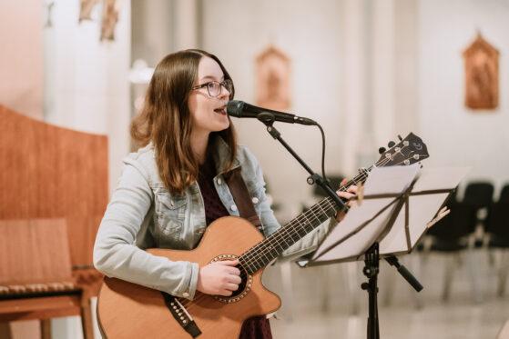 Bild von Hannah Stienen als Sängerin, wie sie live in einer Kirche singt und sich auf der Gitarre begleitet.